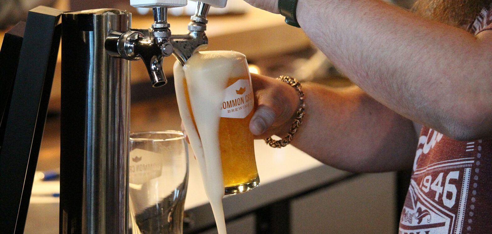 man taps beer on the go